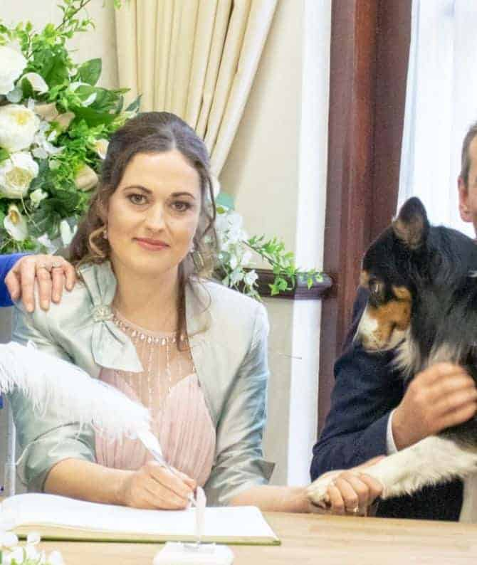 Bride with her dog on wedding day, signing register.