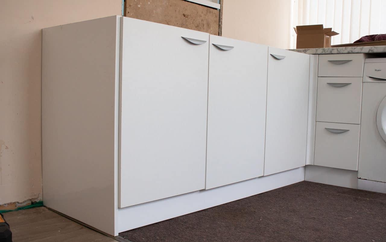 white kitchen plinth in corner kitchen
