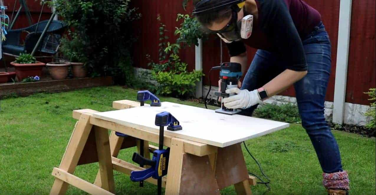 woman routering pine top with 45 degree chamfer router bit