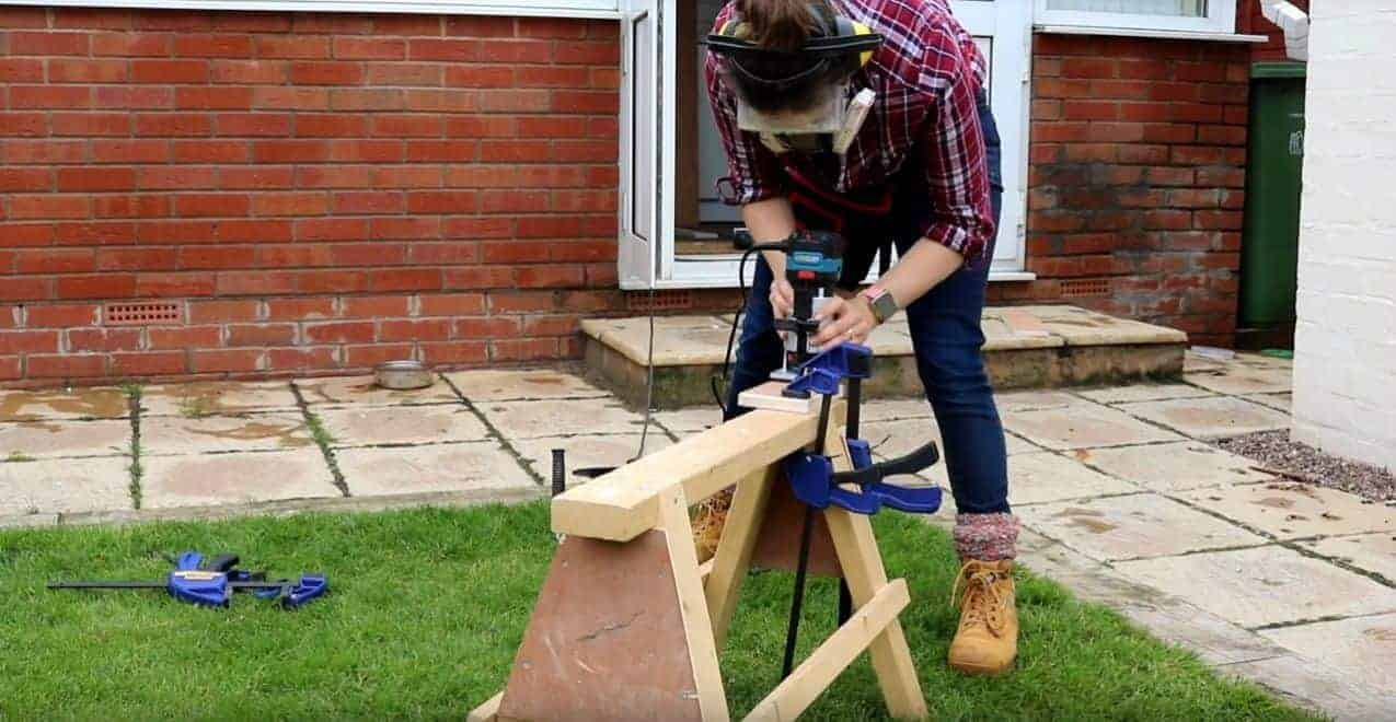 woman wearing safety geat while routering clamped plywood to sawhorses usig chamfer bit